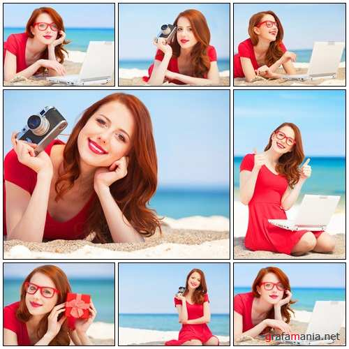 Redhead girl with camera on the beach - Stock Photo