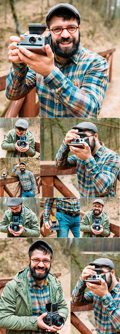 Young man with beard photographs movie in wood