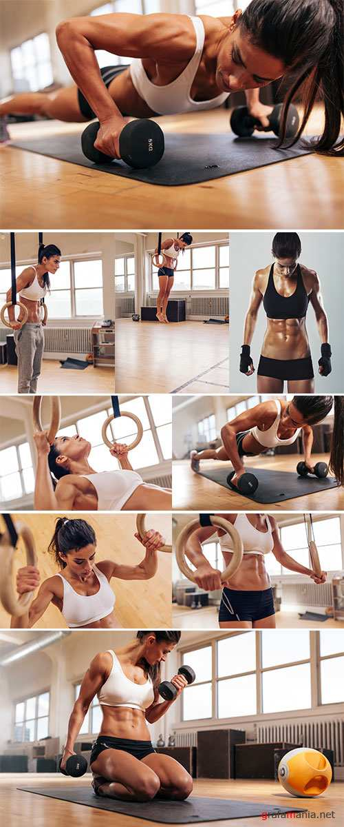 Muscular woman going pull-ups with gymnastic rings - Stock Image