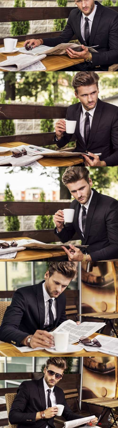 A man in a suit reading a newspaper and drinking coffee